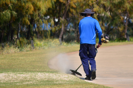 GOLD COAST, AUS - OCT 16 2014:Worker cutting grass.According to the 2010 National Gardening Association Survey, Americans spend on average $363 per year on their lawn and gardening activities. Editorial