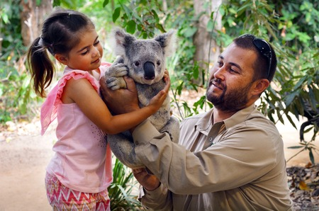GOLD COAST, AUS - NOV 04 2014:Little girl (Talya Ben-Ari age 05) holding a Koala with Zookeeper in Currumbin Wildlife Sanctuary Gold Coast Queensland, Australia.Koalas cannot be kept legally as pets. Editorial