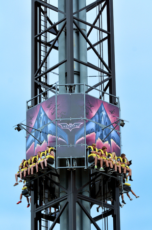 mph: GOLD COAST, AUS -  NOV 06 2014:Visitors ride on Batwing Spaceshot in Movie World Gold Coast Queensland Australia.Riders experience travel up to 4 Gs force at a speed of 64 kilometres per hour 40 mph