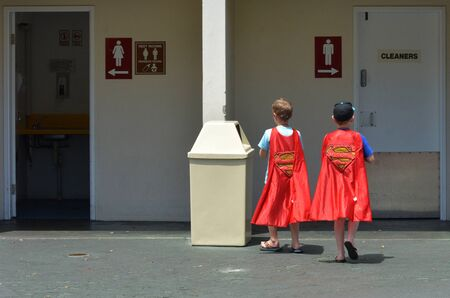 identidad cultural: GOLD COAST, AUS -  NOV 06 2014:Young men wearing Superman costume.Superman is an American cultural icon and has been labeled as the greatest comic book hero of all time by IGN.