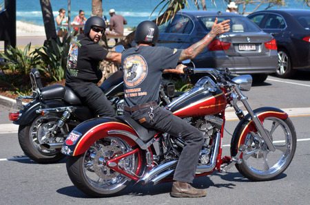 rebelling: GOLD COAST - OCT 09 2014:Men ride Harley-Davidson motorcycle in city street.Harley-Davidson sustains a large brand community which keeps active through clubs and events.