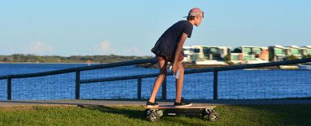 MOTORIZADO: GOLD COAST - OCT 14 2014:Young man rid on motorized skateboard.Its a four wheel drive motorised skateboard capable of reaching 50kmh.