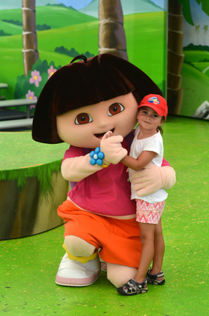 latina america: GOLD COAST, AUS -  NOV 06 2014:Litlle girl Talya Ben-Ari age 04 with Dora the Explorer.Dora teaches Spanish in the U.S., AUS Canada, NZL and Ireland, but teaches English in the rest of the world.