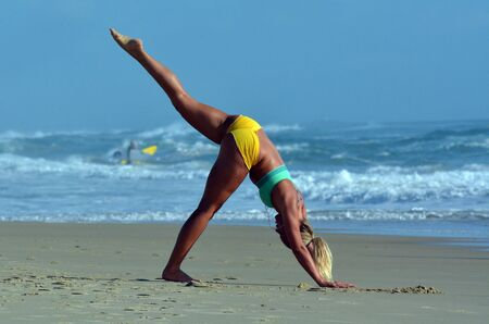 surfers paradise: SURFERS PARADISE - NOV 14 2014:Woman exercise Yoga on the beach.Many studies tried to determine Yoga effectiveness as complementary intervention for cancer, schizophrenia, asthma, and heart disease. Editorial