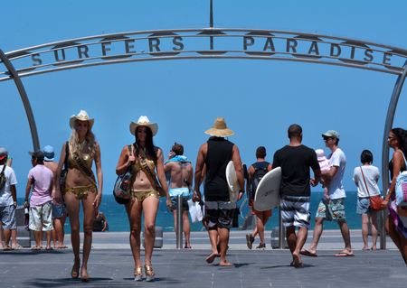 surfers: SURFERS PARADISE - NOV 15 2014Meter Maids and surfers under surfers paradise arch.Its Australias iconic coastal tourist destinations drawing 10 million tourists a year from all over the world.