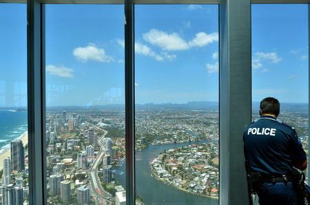 be alert: SURFERS PARADISE - NOV 14 2014:Police officer patrols in Skypoint observation deck.Gold Coast police on high terror alert warned to be hyper vigilant and patrol local mosques and critical infrastructure sites