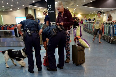 sniffer: AUCKLAND, NZL - NOV 22 2014:Biosecurity officers with sniffer dog on duty.New Zealand has very strict biosecurity procedures at airports and ports to prevent the introduction of pests and diseases.