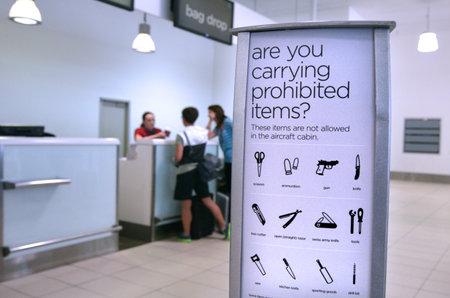 Gold Coast, AUS - 22 november 2014: Passagiers in de check-in desk.For de veiligheid en de veiligheid in de luchtvaart reizigers luchtvaartmaatschappijen hebben bepaalde items verboden gebracht op vliegtuigen in handbagage Andor gecontroleerd zakken.