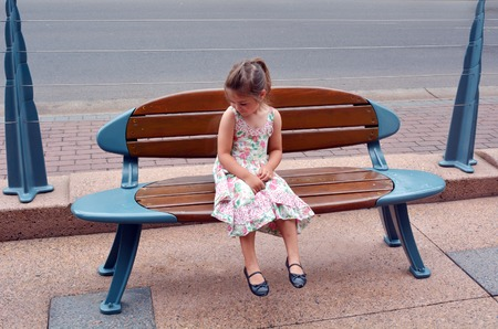 tourist destination: SURFERS PARADISE - NOV 18 2014:Little girl Talya Ben-Ari age 04 sit on a bench in a shape of a surfing board in Surfers Paradise, one of Australias iconic coastal tourist destination.