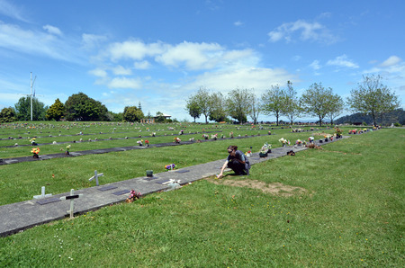 two and two thirds: AUCKLAND, NZL - NOV 23 2014:Woman visit her grandfather grave. Of the roughly 150,000 people who die each day across the globe, about two thirds 100,000 per day die of age-related causes. Editoriali