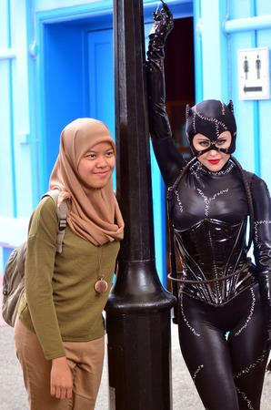 catwoman: GOLD COAST, AUS -  NOV 06 2014:Muslim woman with Catwoman in Movie World Gold Coast Queensland Australia.Catwoman was ranked 23rd in Comics Buyers Guides 100 Sexiest Women in Comics list. Editorial