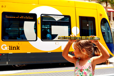 surfers paradise: GOLD COAST, AUS - NOV 14 2014:Child Talya Ben-Ari age 04 hold a replica of Gold Coast Light Rail G in Surfers Paradise Av in Gold Coast Queensland, Australia.The line opened on July 2014 and it 13 Km 8.1 mi long.