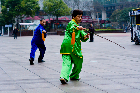 femal: SHANGHAI, CN - MAR 17 2015:Chinese couple practice Tai Chi in Nanjing Road Shanghai China.It is an internal Chinese martial art practised for both its defense training and its health benefits.