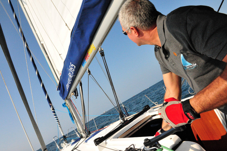 skipper: ASHDOD - SEPTEMBER 20:A yacht master skipper sails his yacht at sea on September 20 2010 in Ashdod, Israel.The term originated from the Dutch Jacht meaning hunt - yacht used by the Dutch navy to catch pirates.