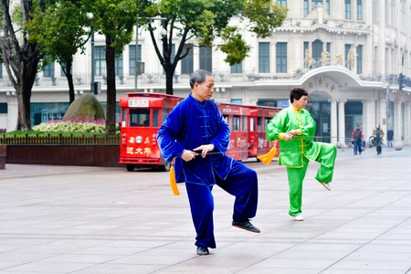 martial artist: SHANGHAI, CN - MAR 17 2015:Chinese couple practice Tai Chi in Nanjing Road Shanghai China.It is an internal Chinese martial art practised for both its defense training and its health benefits.