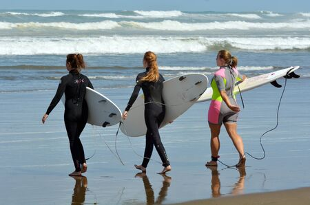 going for it: MURIWAI, NZL -  JAN 01 2015:Girls going to surf in Muriwai beach.Its a very popular beach in New Zealand known for it beauty and for its outdoor activities such as swimming, surfing, biking and fishing.
