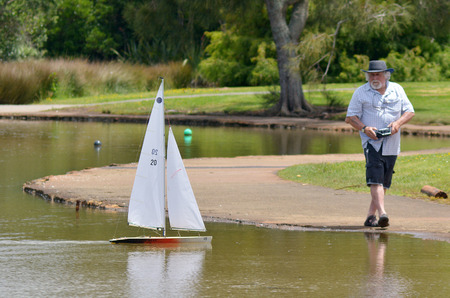 remote controlled: AUCKLAND, NZL - DEC 21 2014: Man sails a remote controlled sailing wooden yacht in a pond.Radio-controlled boats are the most common type of boat amongst casual hobbyists.