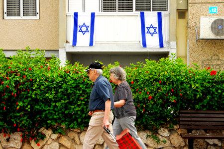 israeli: ASHDOD - MAY 15: An Israeli old couple pass by tow Israeli national flages  Israel during IIsrael Independence Day - Yom Haatzmaut on May 15 2006 in Ashdod, Israel.
