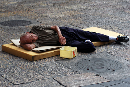 JERUSALEM - NOVEMBER 15: A street beggar lies on the ground and begs for money on November 15 2007 in Jerusalem, Israel.About 20.5 of Israeli families living below the poverty line