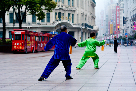 practised: SHANGHAI, CN - MAR 17 2015:Chinese couple practice Tai Chi in Nanjing Road Shanghai China.It is an internal Chinese martial art practised for both its defense training and its health benefits.