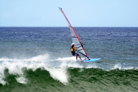 invented: HAIFA - AUG 20:Windsurfer is windsurfing  on August 20 2006 in Haifa bay, Israel. Sailboarding was invented in 1970 involving travel over water powered by wind on a single sail.