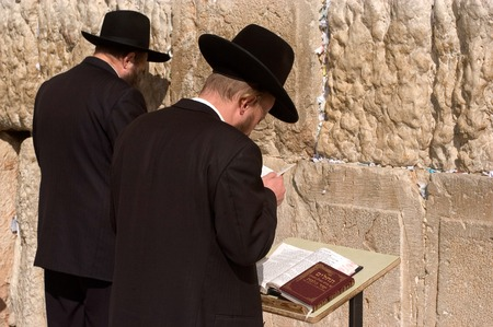 tora: JERUSALEM - AUGUST 11:Jewish men are praying at the western wall on August 11 2005 in Jerusalem, Israel.It is a remnant of the ancient wall that surrounded the Jewish Temples and is the most sacred site recognized by the Jewish faith outside of the Templ