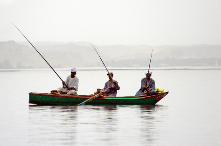 villagers: Nubian Egyptian villagers men are fishing in the Nile river, Egypt.