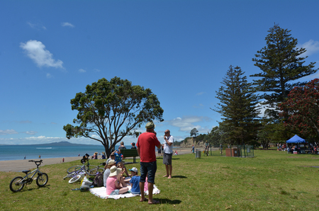 browns: AUCKLAND, NZL - DEC 21 2014:Visitors on Browns Bay beach.Browns Bay is a very popular tourist destination on Auckland North Shore, New Zealand.
