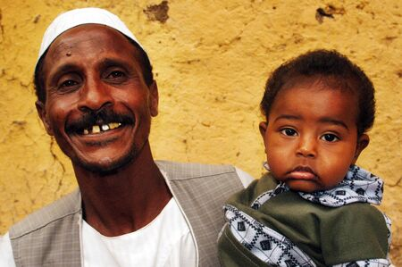 village man: Egyptian Nubian man and his baby in a village on the Nail river, Egypt.