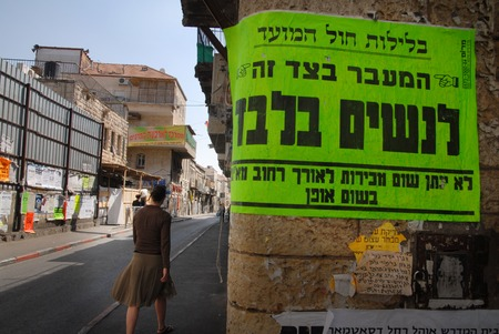 mea: Ultra orthodox jewish woman passing by a  street sign reads: PASSING IS ALLOW TO  WOMAN ONLY in Mea Shearim, ultra orthodox neighbourhood Jerusalem, Israel. Editorial