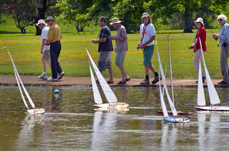 governed: AUCKLAND, NZL - DEC 21 2014:People racing remote controlled sailing wooden yachts in a pond.The racing is governed by the same Racing Rules of Sailing that are used for full-sized crewed sailing boats