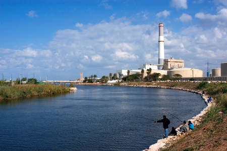tel: Fisherman fishing on the Yarkon River in Tel Aviv, Israel.
