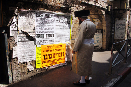 shearim: JERUSALEM- SEPTEMBER 28: An Ultra orthodox jewish man reads a street sign says: PASSING IS ALLOW TO MAN ONLY on September 28 2007 in Mea Shearim, ultra orthodox neighbourhood Jerusalem, Israel.It is one of the oldest Jewish neighborhoods in Jerusalem, Isr Editorial