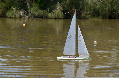 remote controlled: AUCKLAND, NZL - DEC 21 2014:One remote controlled sailing wooden yacht race in a pond.The racing is governed by the same Racing Rules of Sailing that are used for full-sized crewed sailing boats