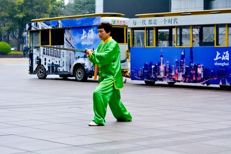 taichi: SHANGHAI, CN - MAR 17 2015:Chinese woman practice Tai Chi in Nanjing Road Shanghai China.It is an internal Chinese martial art practised for both its defense training and its health benefits.