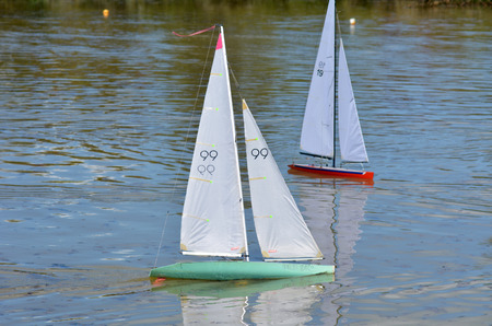 governed: AUCKLAND, NZL - DEC 21 2014:Two remote controlled sailing wooden yachts race in a pond.The racing is governed by the same Racing Rules of Sailing that are used for full-sized crewed sailing boats