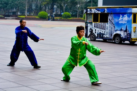 taichi: SHANGHAI, CN - MAR 17 2015:Chinese couple practice Tai Chi in Nanjing Road Shanghai China.It is an internal Chinese martial art practised for both its defense training and its health benefits.