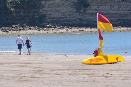ban aid: AUCKLAND - DEC 21 2014:Couple walks beside a Yellow and Red Lifeguards flag on the beach. In 20013 98 people drowned in New Zealand. NZ has the 3rd highest drowning rate in the developed world. Editorial