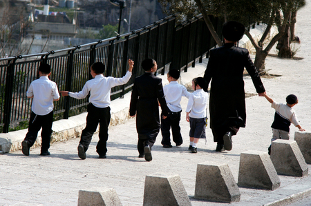 JERUSALEM - OCTOBER 24: An ultra orthodox jewish family walking in the street on October 24 2007 in Jerusalem old city, Israel.An Israel ultra-Orthodox families are producing 5 to 10 children each. Éditoriale