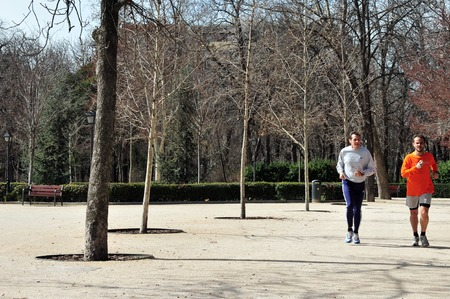 Spanish men are running and jogging  in Retiro Park Parque del Retiro is a huge urban park located in Madrid Spain.  The park features formal gardens, natural forests, a lake, a crystal palace and many beautiful sculptures and statues. Visitors to Madri Editorial