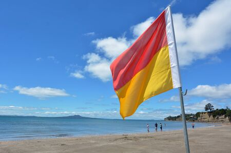 coastguard: AUCKLAND - DEC 21 2014:Red and yellow flags. NZL Government urge to stump up Lifesavers and Coastguard operations, as 2013 OECD report show NZ has the 3rd highest drowning rate in the developed world. Editorial