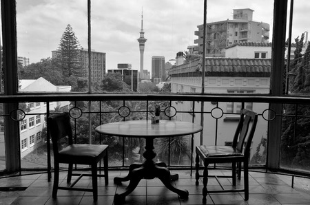 sky scraper: AUCKLAND - JAN 09 2015:Two empty chairs and a table against. Auckland CBD skyline.The 2014 Mercer Quality of Living Survey ranked Auckland 3rd place in the world on its list. BW Editorial