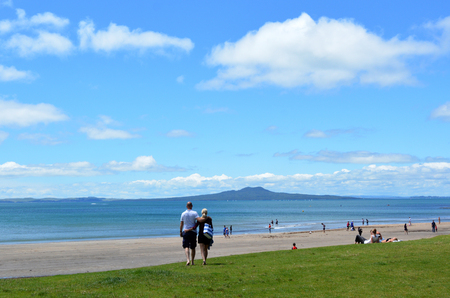 browns: AUCKLAND, NZL - DEC 21 2014:Visitors on a beach overlooking Rangitoto Island.The 5.5 km wide island is an iconic landmark of Auckland with distinctive symmetrical volcano cone rising 260 m 850 ft high Editorial