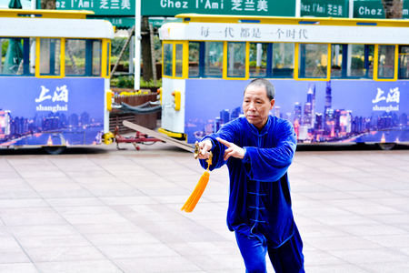taichi: SHANGHAI, CN - MAR 17 2015:Chinese man practice Tai Chi in Nanjing Road Shanghai China.It is an internal Chinese martial art practised for both its defense training and its health benefits. Editorial