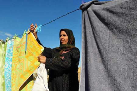 WESTERN NEGEV - 26. November: Eine beduinische Frau aus Lakyia Beduinendorf im Süden Israels hängt Kleidung auf einer Wäscheleine am 26. November 2008.egev Beduinen früher nomadischen sind und später auch halb-nomadischen Arabern, die von der Viehzucht in der Wüste leben Standard-Bild - 46309523