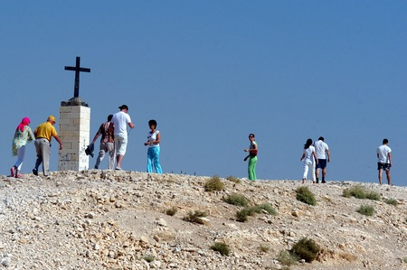 holyland: JERICHO, ISR - OCT 21:Visitors under a cross of St. Georges Monastery on Oct 21 2006.The Greek Orthodox monastery was built in the late 5th century A.D. by John of Thebes. Editorial