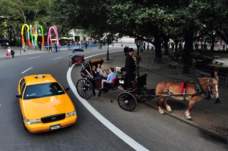 taxicabs: Yellow Taxi cab and horse carriage Central Park transpiration Manhattan New York, USA.