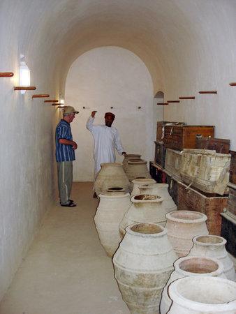 guia turistico: Rustaq dec 23: giras omaní guía muestran artefactos de Al Hazm Fort en 23 de diciembre 2007 cerca de Rustaq, Oman.It es un ejemplo sobresaliente de la arquitectura islámica de Omán y fue construido en 1711 AD.