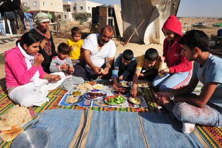 arabic food: Lakiya, ISR - 12 de diciembre: los musulmanes comer carne de cordero en el Eid al-Adha, 08 de diciembre de 2008. El Festival se celebra mediante el sacrificio de un cordero u otro animal y distribuci�n de la carne a sus familiares, amigos, y los pobres. Editorial
