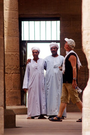 egypt revolution: ASWAN - APRIL 29:Egyptian tour guides and a visitor in Temple of Philae on April 29 2007 near Aswan, Egypt. The number of tourists visiting Egypt dropped by more than a third since the Egyptian revolution on Jan 25 2011.